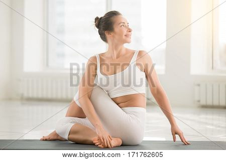 Young smiling attractive woman practicing yoga, sitting in Half lord of the fishes exercise, Ardha Matsyendrasana pose, working out, wearing sportswear, sport bra, pants, full length, white background
