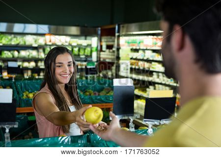 Smiling woman giving fruit to cashier for billing at supermarket