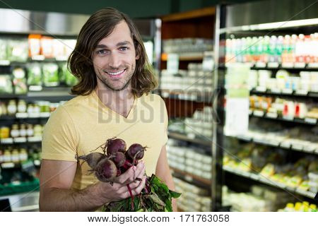 Portrait of smiling man holding bunch of beetroots in supermarket