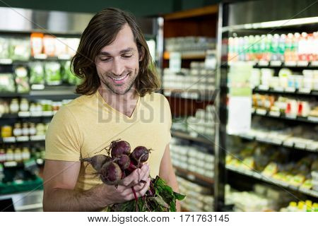 Smiling man holding bunch of beetroots in supermarket