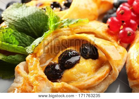 Tasty puff pastry with berries on plate, closeup