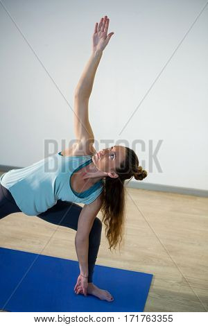 Woman performing extended side angle pose on exercise mat in fitness studio