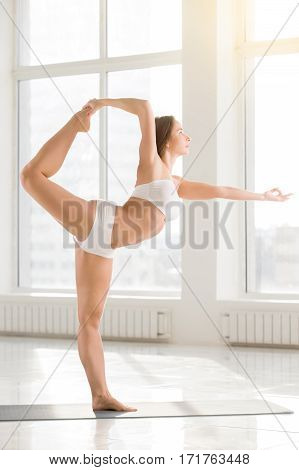 Young attractive yogi woman practicing yoga, standing in Lord of the Dance exercise, Natarajasana pose, working out wearing sportswear, sport bra, shorts, indoor full length, white color background
