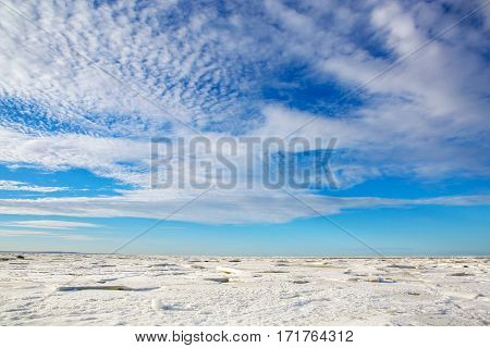 The idyllic panorama of the North sea frozen in the ice. Beautiful nature water frozen in the winter. Landscape snowy expanse to the horizon with a wonderful sky and clouds.