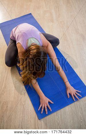 Woman doing cross legged forward fold on exercise mat in fitness studio
