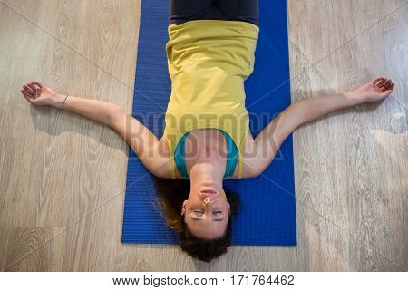 Woman doing yoga corpse pose on exercise mat in fitness studio