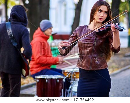 Violin woman outdoor. Festival music band. Friends playing on percussion instruments in city park. City and trees in background.