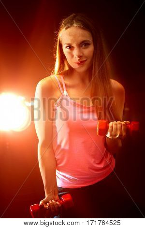 Fitness girl exercising in gym with dumbbells. Woman works in multi-colored rays of sport room. Portrait of full-length in backlit.