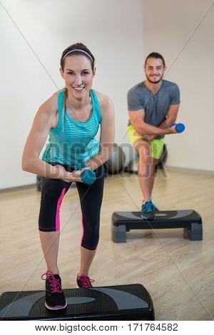 Portrait of man and woman doing aerobic exercise with dumbbell on stepper
