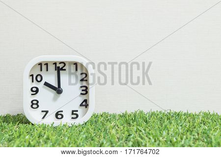 Closeup white clock for decorate in 10 o'clock on green artificial grass floor and cream wallpaper textured background with copy space