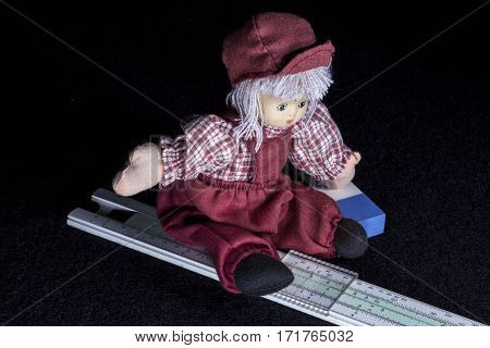 UMEA, SWEDEN ON OCTOBER 01. A Child doll sit on a slide rule and a rubber on its left hand on October 01, 2013 in Umea, Sweden. Black background. Illustrative Editorial