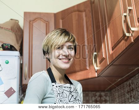Young blond wearing apron posing in a looking messy kitchen lifestyle cropped portrait