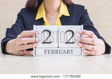 Closeup white wooden calendar with black 22 february word in blurred working woman hand on wood desk in office room in selective focus at the calendar