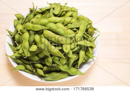 Boiled green soybeans heaping on a white dish