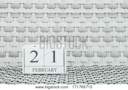 Closeup surface white wooden calendar with black 21 february word on blurred weave wood chair textured background with copy space in selective focus at the calendar