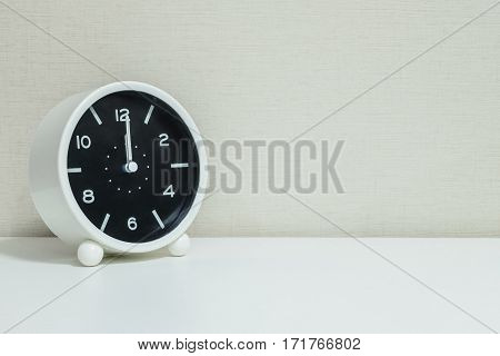 Closeup black and white alarm clock for decorate in 12 o'clock on white wood desk and cream wallpaper textured background with copy space