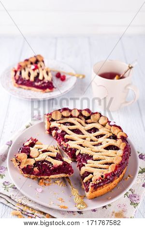 Tart, pie, cake with jellied fresh cranberries, bilberries and winter spices on a brown wooden background