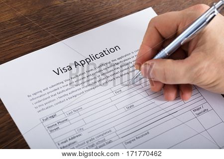 Close-up Of A Person Hand Filling Visa Application Form On Wooden Desk