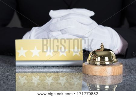 Close-up Of A Waiter Hand Near Service Bell And Five Star Shape Card