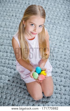 Cite little girl holding colorful Easter eggs and smiling