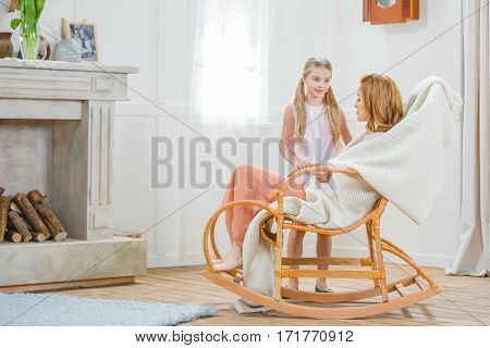Young mother sitting in rocking chair and her little daughter standing nearby