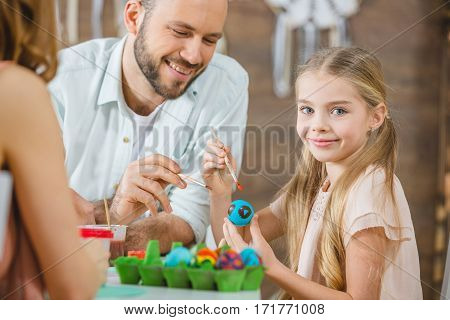 Little girl sitting at table and painting Easter eggs with her parents
