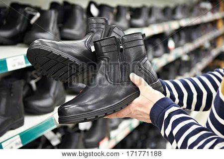 Winter Boots In Hands Of Man Customers At Store