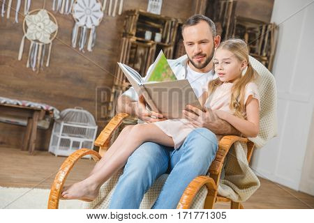 Father and daughter sitting together in rocking chair and reading book