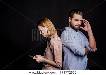 Young woman using smartphone while standing back to back with pensive man