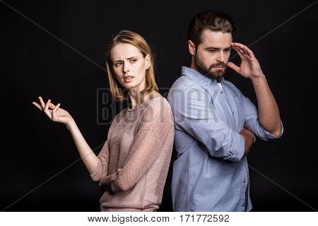 Young man and woman disappointed standing back to back on black
