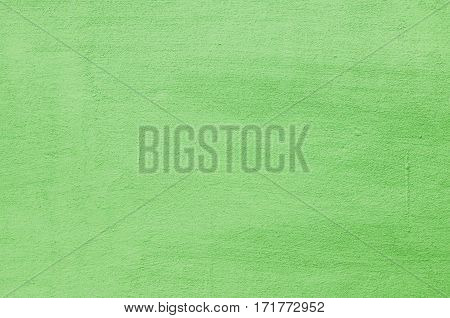 Background of a green stucco coated and painted exterior, rough cast of cement and concrete wall texture, decorative coating