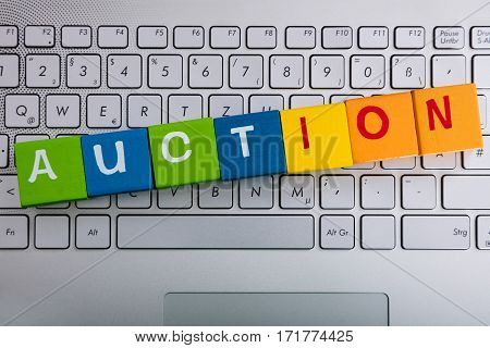 High Angle View Of Auction Word On Colorful Cubes Over Laptop Keyboard