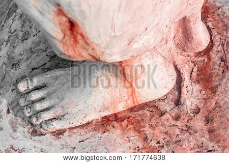 Extreme close-up of the feet of Jesus Christ bloodied. Top view. Shallow depth of field.