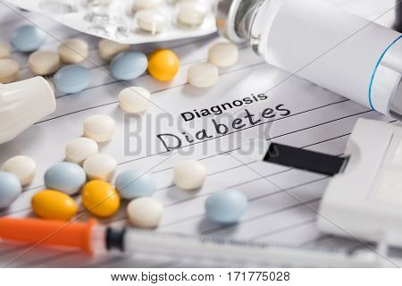 Close-up Of Diabetes Text On White Paper With Pills;Vial And Syringe