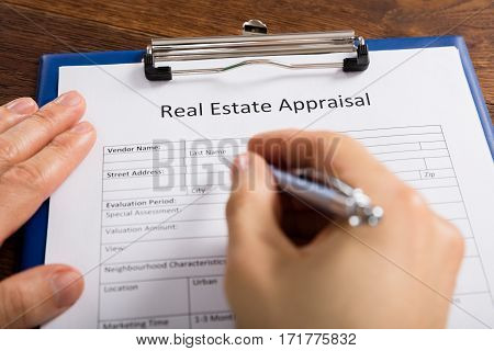 Close-up Of Person Hand Filling Real Estate Appraisal Form With Pen