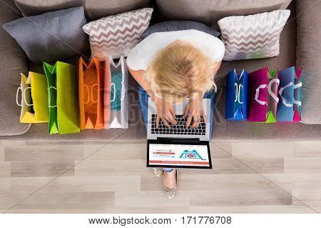 High Angle View Of A Woman Shopping Online On Laptop With Shopping Bags On Couch