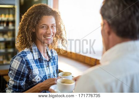 Smiling couple having coffee in café