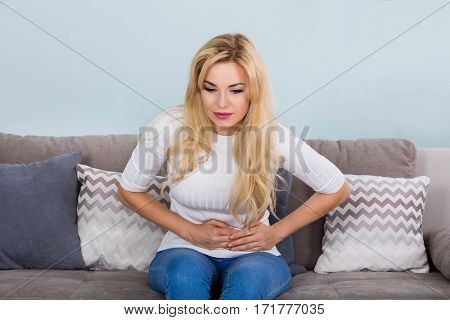 Young Unhappy Woman Suffering From Stomach Ache On Couch At Home