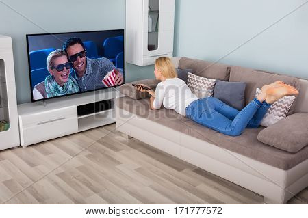 Woman Lying On Couch Watching Movie On TV In Living Room At Home