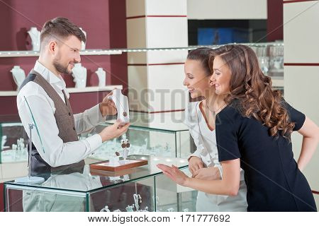 Shopping with a friend. Two beautiful young female friends choosing jewelry at the jewelry store jeweler profession occupation helpful assistance consumerism friendship togetherness feminine concept poster