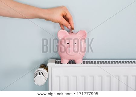 Close-up Of A Woman Hand Inserting Coin In Piggybank On Radiator At Home