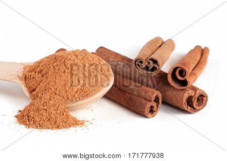 three cinnamon sticks and powder with spoon isolated on white background.