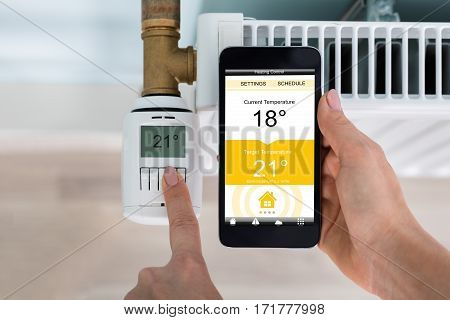 High Angle View Of Person Hand Setting Temperature Of Thermostat Using Mobilephone At Home