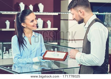 Help of a pro. Professional female jeweler smiling helping her male customer showing him diamond engagement ring to buy service helpful professional job occupation worker shopping people concept