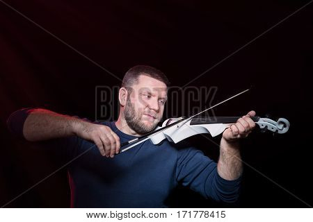 Bearded violinist plays intently on electric violin, isolated on a black background