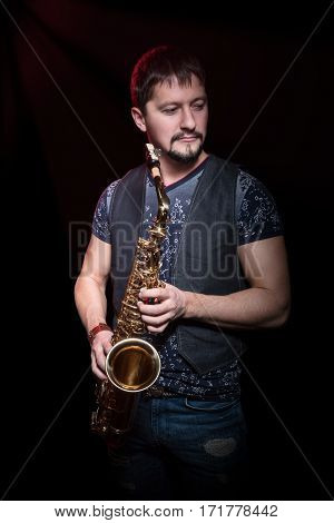 Portrait of a bearded man in a waistcoat with saxophone in hand, isolated on a black background