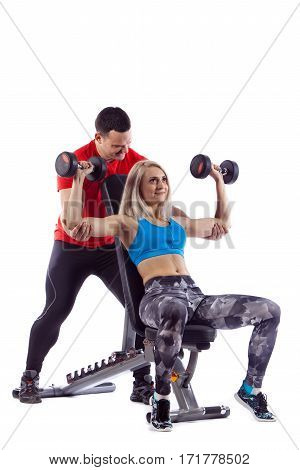 Personal trainer man is teaching woman lifting a dumbbell. Isolated over white background.