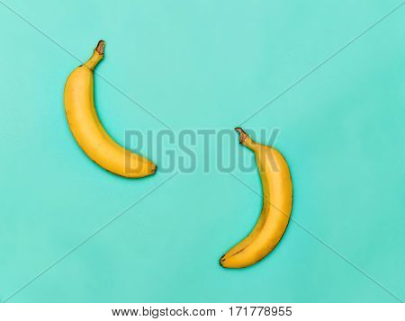 The two fresh bananas against the blue background