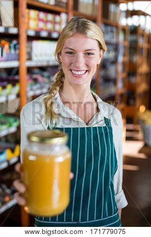 Portrait of smiling female staff holding jar of honey in super market