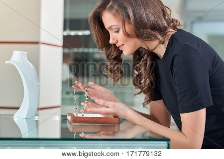 Dream necklace Profile shot of a gorgeous young woman holding a necklace at the jewelry store smiling happily buying jewelry customer consumer consumerism buyer shopper luxury accessories concept .